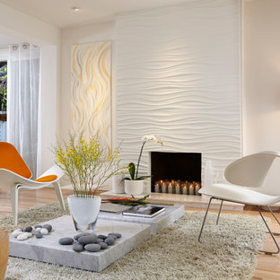 Cette photo montre un salon tendance de taille moyenne avec un mur beige, un sol en bois clair et une cheminée standard.
