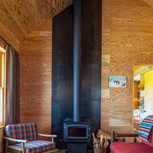 Esempio di un piccolo soggiorno rustico chiuso con stufa a legna, cornice del camino in metallo, nessuna TV e pareti marroni