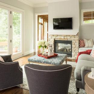 Idéer för att renovera ett vintage vardagsrum, med grå väggar, mellanmörkt trägolv, en dubbelsidig öppen spis och en spiselkrans i sten