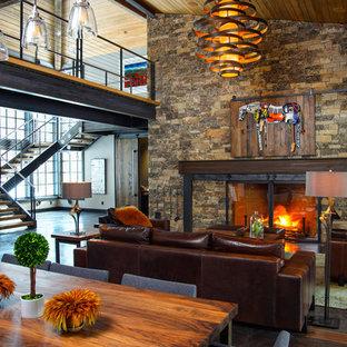 Foto di un soggiorno minimal aperto con sala formale, pareti grigie, pavimento in cemento, camino classico, cornice del camino in pietra e nessuna TV
