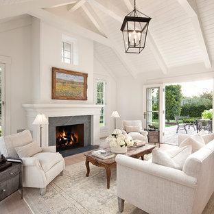 サンタバーバラのトラディショナルスタイルのおしゃれなLDK (白い壁、淡色無垢フローリング、標準型暖炉、石材の暖炉まわり、フォーマル) の写真