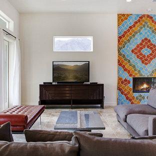 Esempio di un grande soggiorno mediterraneo aperto con pareti bianche, pavimento in cemento, camino classico, cornice del camino piastrellata e TV autoportante