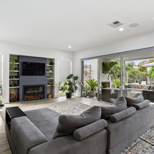 Photo of a contemporary open concept living room in Perth with white walls, medium hardwood floors, a ribbon fireplace, a wall-mounted tv and brown floor.