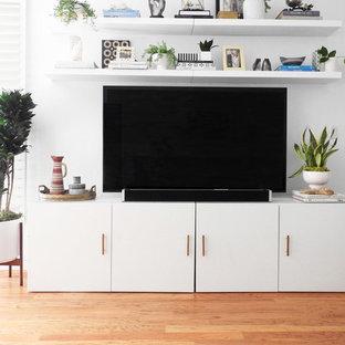 ニューヨークの中サイズのビーチスタイルのおしゃれなLDK (白い壁、無垢フローリング、コーナー設置型暖炉、木材の暖炉まわり、据え置き型テレビ、茶色い床) の写真