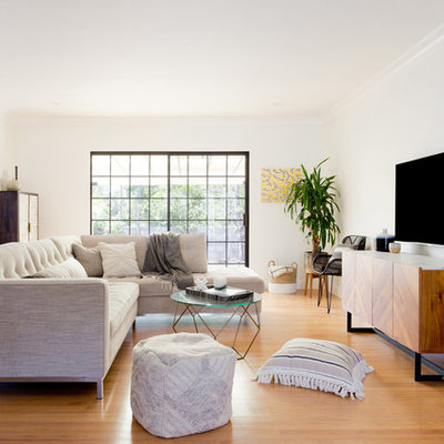 Example of a mid-sized trendy open concept medium tone wood floor and brown floor living room design in Los Angeles with white walls, a wall-mounted tv and no fireplace