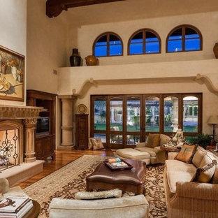 フェニックスの巨大な地中海スタイルのおしゃれなリビングロフト (フォーマル、ベージュの壁、濃色無垢フローリング、標準型暖炉、コンクリートの暖炉まわり、テレビなし、茶色い床) の写真