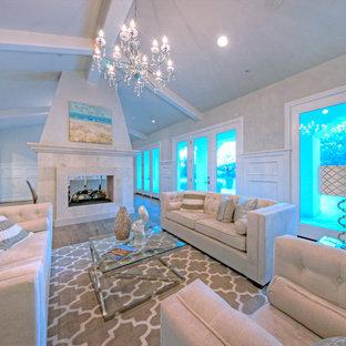 Foto di un grande soggiorno mediterraneo aperto con sala formale, pareti beige, parquet chiaro, camino bifacciale e cornice del camino in pietra