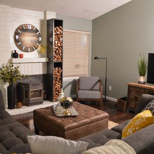 Diseño de salón abierto, rural, de tamaño medio, con paredes grises, suelo de madera oscura, estufa de leña, televisor independiente y suelo marrón