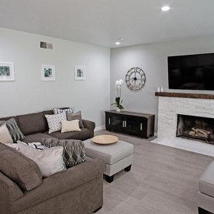 Esempio di un soggiorno minimal di medie dimensioni e chiuso con pareti verdi, pavimento in laminato, camino classico, cornice del camino in pietra, TV a parete e pavimento grigio