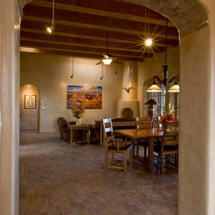 アルバカーキの大きいサンタフェスタイルのおしゃれなLDK (フォーマル、ベージュの壁、レンガの床、コーナー設置型暖炉、コンクリートの暖炉まわり、テレビなし、ベージュの床) の写真