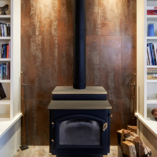 Living room library - mid-sized traditional enclosed medium tone wood floor and brown floor living room library idea in Seattle with brown walls, a wood stove and a metal fireplace