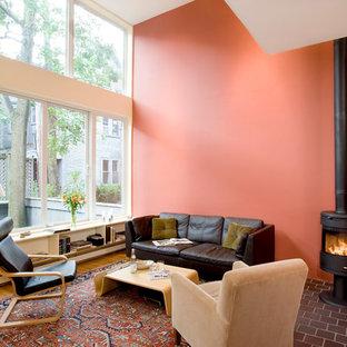 Imagen de salón para visitas abierto, clásico renovado, de tamaño medio, sin televisor, con paredes rosas, suelo de ladrillo y estufa de leña