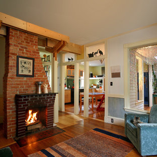 Inspiration for a mid-sized eclectic enclosed dark wood floor living room remodel in Boston with a standard fireplace, a brick fireplace, white walls and no tv