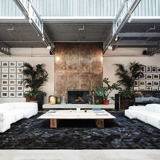 Photo of an expansive industrial open plan living room in London with white walls, concrete flooring, a standard fireplace, a metal fireplace surround, a freestanding tv and grey floors.