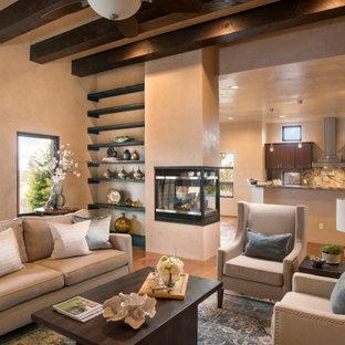 アルバカーキのサンタフェスタイルのおしゃれなLDK (ベージュの壁、コンクリートの床、コーナー設置型暖炉、漆喰の暖炉まわり、オレンジの床) の写真