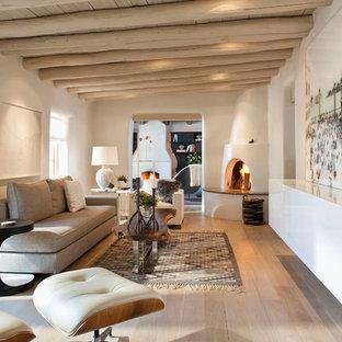 アルバカーキの中くらいのサンタフェスタイルのおしゃれな独立型リビング (コーナー設置型暖炉、白い壁、淡色無垢フローリング、漆喰の暖炉まわり) の写真