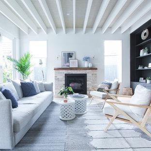 シドニーの大きいビーチスタイルのおしゃれなLDK (フォーマル、白い壁、淡色無垢フローリング、薪ストーブ、レンガの暖炉まわり、据え置き型テレビ) の写真