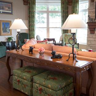 Aménagement d'un grand salon classique fermé avec un mur gris, un sol en bois brun, une cheminée standard, un manteau de cheminée en pierre, un téléviseur fixé au mur, un sol marron et une salle de réception.