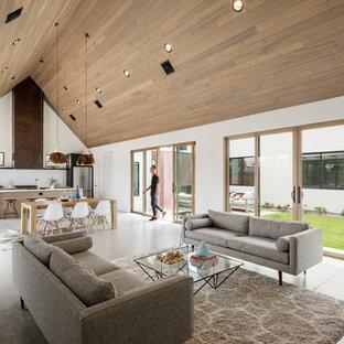 フェニックスのサンタフェスタイルのおしゃれなLDK (白い壁、コンクリートの床、壁掛け型テレビ、グレーの床) の写真