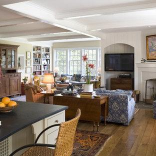 フィラデルフィアの広いトラディショナルスタイルのおしゃれなLDK (ベージュの壁、無垢フローリング、コーナー設置型暖炉、木材の暖炉まわり、埋込式メディアウォール) の写真