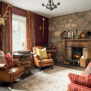 This is an example of an eclectic formal living room in London with dark hardwood flooring and a wood burning stove.