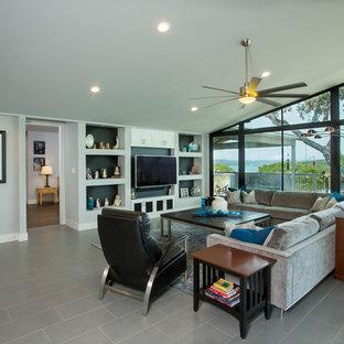 オースティンの中サイズのビーチスタイルのおしゃれなLDK (グレーの壁、磁器タイルの床、壁掛け型テレビ) の写真