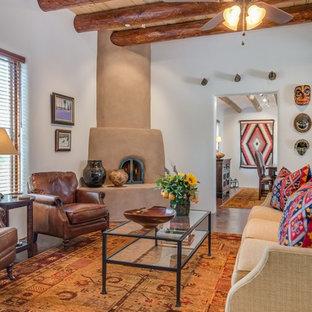 Inspiration för ett mellanstort amerikanskt separat vardagsrum, med ett finrum, vita väggar, betonggolv, en öppen hörnspis, en spiselkrans i gips och brunt golv