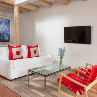 Example of a southwest open concept brick floor living room design in Albuquerque with white walls and a wall-mounted tv