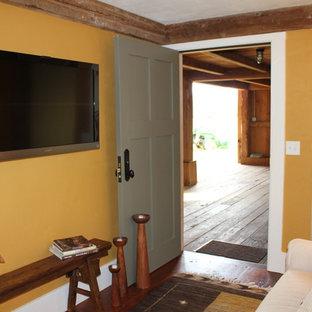 Idee per un piccolo soggiorno country chiuso con TV a parete, parquet scuro, nessun camino e pareti arancioni