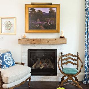 Idées déco pour un salon avec une bibliothèque ou un coin lecture classique de taille moyenne et fermé avec un mur blanc, un sol en vinyl, une cheminée standard, un manteau de cheminée en pierre et aucun téléviseur.