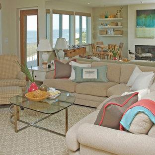 他の地域の中くらいのビーチスタイルのおしゃれなLDK (標準型暖炉、カーペット敷き、ベージュの床、グレーの壁) の写真