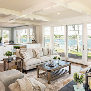 Example of a coastal open concept medium tone wood floor and brown floor living room design in Boston with white walls, no fireplace and no tv