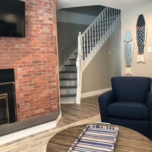 フィラデルフィアの中サイズのビーチスタイルのおしゃれなLDK (ベージュの壁、クッションフロア、標準型暖炉、レンガの暖炉まわり、壁掛け型テレビ、グレーの床) の写真
