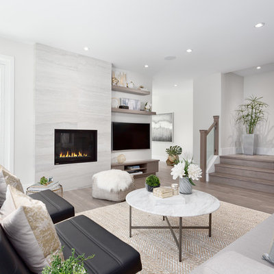 Example of a mid-sized trendy open concept and formal medium tone wood floor and brown floor living room design in Vancouver with gray walls, a wall-mounted tv, a standard fireplace and a stone fireplace