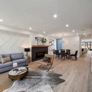 Mittelgroßes, Offenes Modernes Wohnzimmer mit weißer Wandfarbe, hellem Holzboden, Kamin, gefliester Kaminumrandung und Wandpaneelen in Washington, D.C.