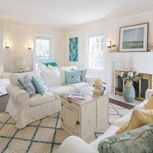 Ispirazione per un soggiorno costiero chiuso con pareti gialle, camino classico, cornice del camino in mattoni e nessuna TV