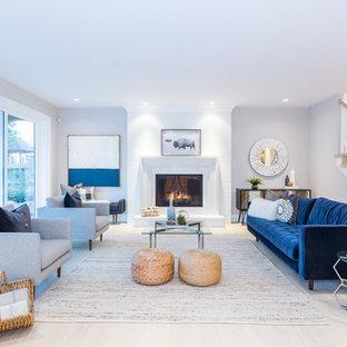 Esempio di un grande soggiorno costiero con sala formale, parquet chiaro, camino classico, cornice del camino in intonaco, pavimento beige e pareti grigie