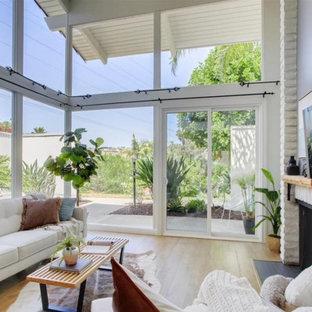 サンディエゴの広いミッドセンチュリースタイルのおしゃれなLDK (白い壁、無垢フローリング、標準型暖炉、レンガの暖炉まわり、壁掛け型テレビ、茶色い床、三角天井、レンガ壁) の写真