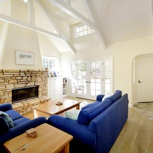 サンフランシスコの中サイズのラスティックスタイルのおしゃれなLDK (淡色無垢フローリング、標準型暖炉、石材の暖炉まわり、白い壁、テレビなし、茶色い床) の写真