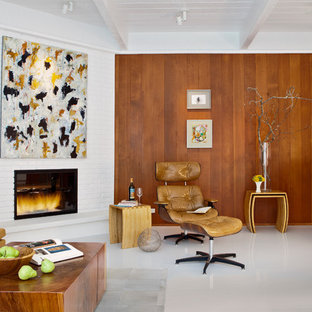 This is an example of a midcentury living room in San Francisco with a brick fireplace surround, a corner fireplace and white floor.