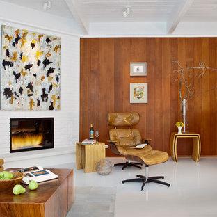 Foto di un soggiorno moderno con cornice del camino in mattoni, camino ad angolo e pavimento bianco