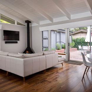 Diseño de salón para visitas abierto, vintage, de tamaño medio, con paredes grises, suelo de madera oscura, chimeneas suspendidas, marco de chimenea de metal, televisor colgado en la pared y suelo marrón