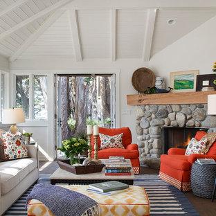 デンバーのビーチスタイルのおしゃれなリビング (白い壁、濃色無垢フローリング、コーナー設置型暖炉、石材の暖炉まわり) の写真