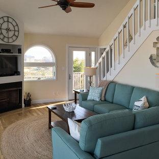 Ispirazione per un soggiorno stile marinaro di medie dimensioni e aperto con pareti beige, pavimento in vinile, camino ad angolo e cornice del camino in legno