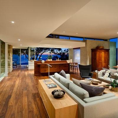 Trendy open concept medium tone wood floor and brown floor living room photo in Santa Barbara with beige walls