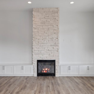 This is an example of a mid-sized contemporary open concept living room with white walls, laminate floors, a standard fireplace, a wall-mounted tv and white floor.