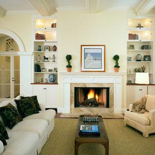 Foto di un soggiorno classico con cornice del camino in pietra e pareti gialle