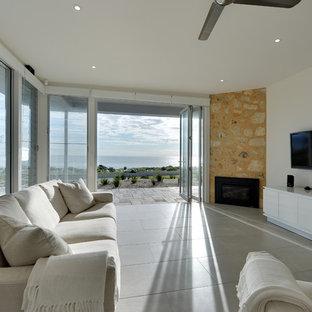 アデレードの広いビーチスタイルのおしゃれなLDK (白い壁、セラミックタイルの床、コーナー設置型暖炉、石材の暖炉まわり、壁掛け型テレビ) の写真