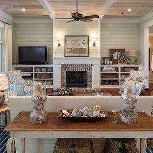 Immagine di un grande soggiorno costiero chiuso con pavimento in legno massello medio, camino classico, cornice del camino in mattoni, pareti beige e TV autoportante