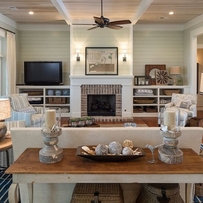 Example of a large beach style enclosed medium tone wood floor living room design in Atlanta with a standard fireplace, a brick fireplace, beige walls and a tv stand